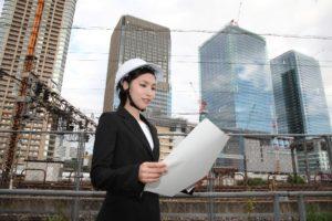 ヘルメットをかぶり図面を見る女性